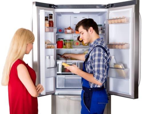 Έλεγχος ψυγείου από μηχανικό, με γυναίκα δίπλα