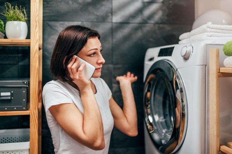 Γυναίκα με τηλέφωνο μπροστά σε πλυντήριο